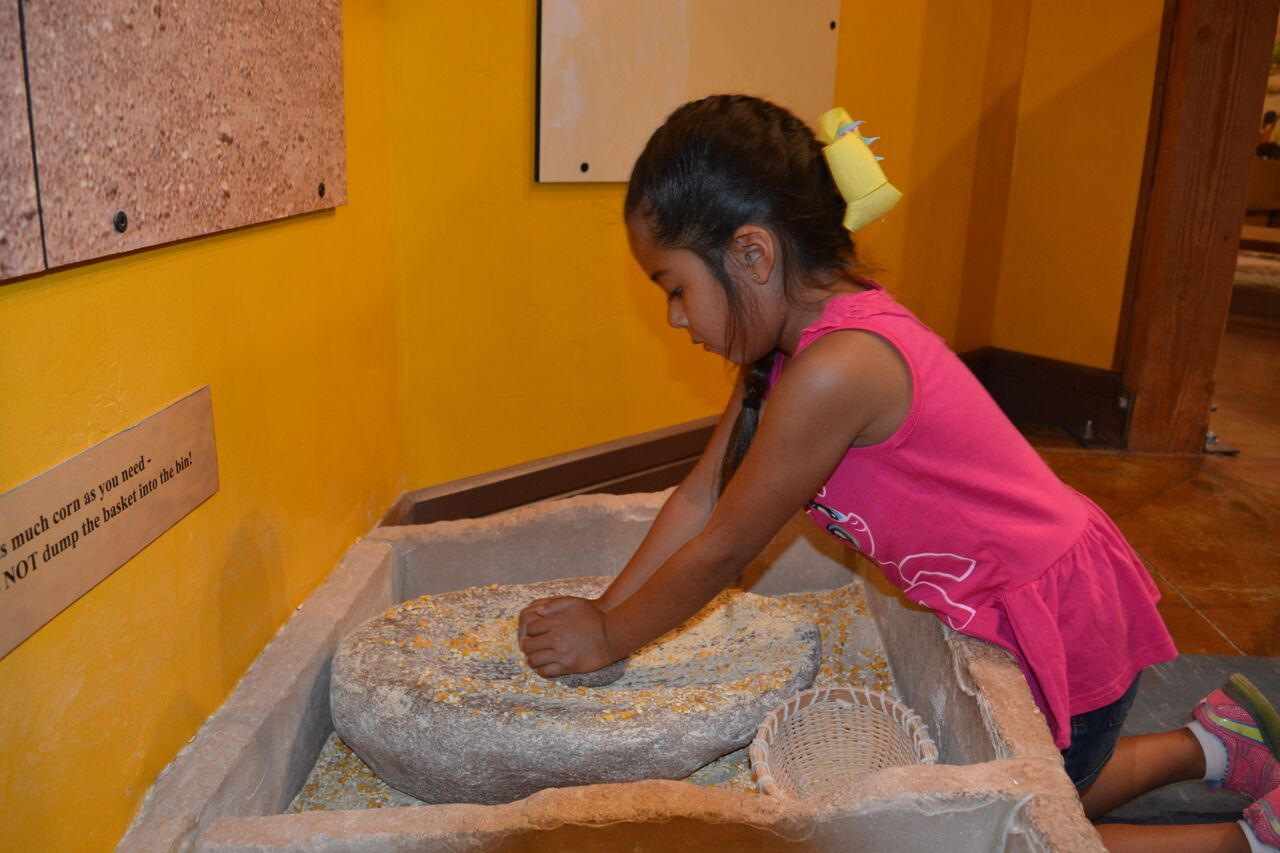 Girl grinding corn with a mano and metate